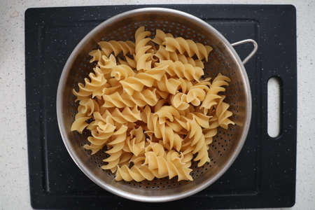 A top view closeup of uncooked swirling pasta in a metal bowl on a grey surface