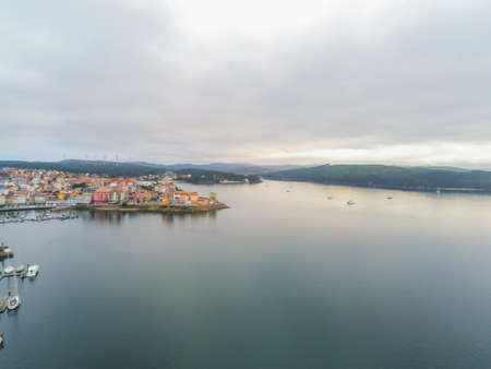 A high angle shot of buildings near the sea under a cloudy sky in Galicia, Spain