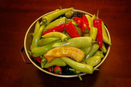 A closeup shot of a colander of red, yellow, and green peppers on a wooden table Banco de Imagens