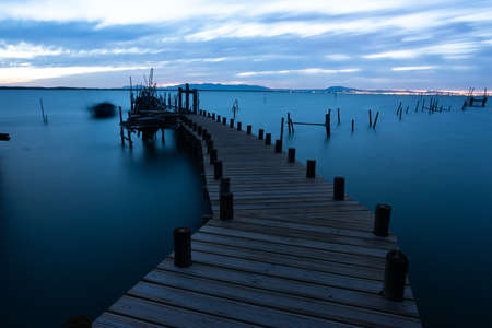 A pier on the sea surrounded by hills under a cloudy sky in the evening in Portugal