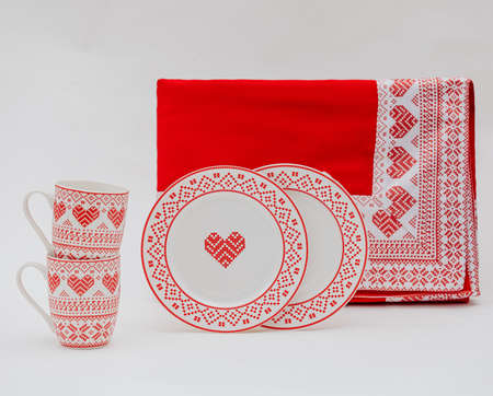 A closeup shot of plates, mugs, and a towel with patterns on a white background