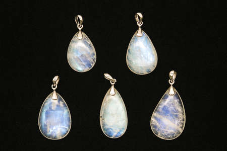 Different pendants made of rainbow moonstone behind a black surface