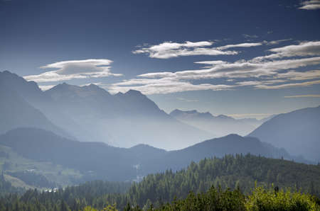 A landscape of mountains covered in greenery and fog under a blue sky in Switzerland