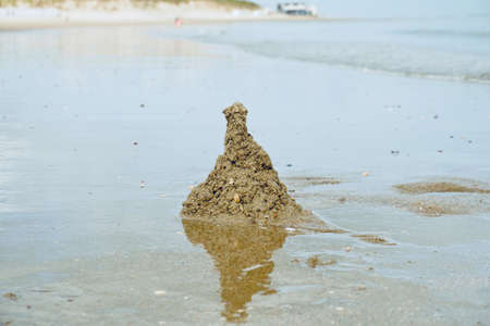 A pile of sand surrounded by the water on the beach