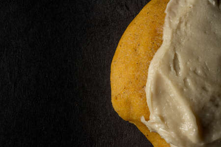 A closeup shot of a biscuit with cream on it