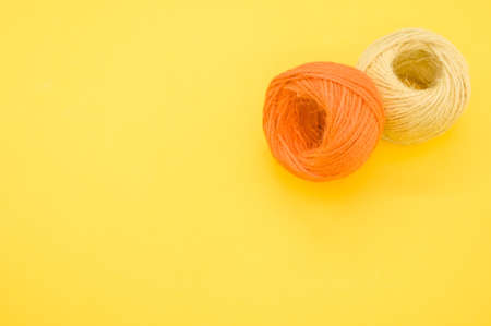 The yarn balls for knitting isolated on yellow background