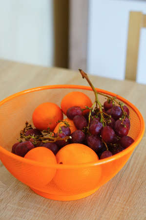 An orange bowl of grapes and oranges on a wooden table