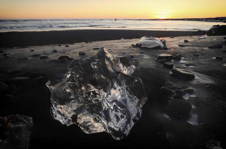 A big block of ice at shore of The Glacier Lagoon, Jokulsarlon, Iceland in Europe, with a sunset in the horizon