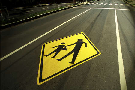 A yellow traffic sign of pedestrians on the road