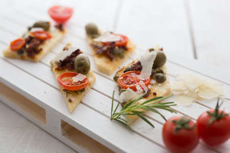 A shot of tasty bruschettas with tomatoes, olives, capers, and cheese served on a wooden board Foto de archivo