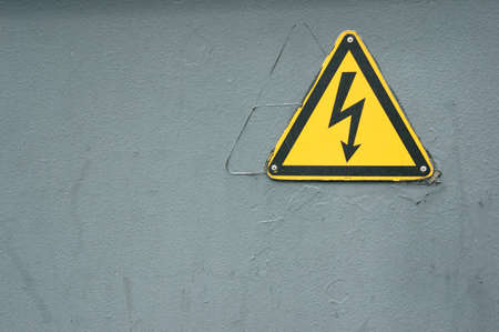 A closeup shot of an electricity warning against a gray wall