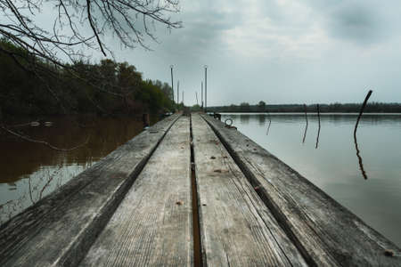 A beautiful shot of a wooden surface on the lake with a cloudy gray sky in the background