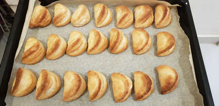 A beautiful shot of crescent-shaped cookies in the black metal pan