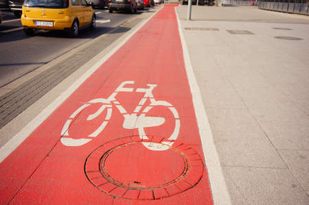POZNAN, POLAND - Mar 05, 2020: Red colored bicycle route next to a road in the city center.