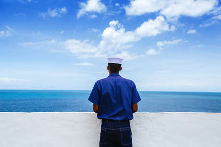 Sailor contemplates the Ocean on Sailors day in Forte Santo Antonio da Barra under a blue sky with beautiful white clouds, Salvador da Baía - Brazil Banco de Imagens