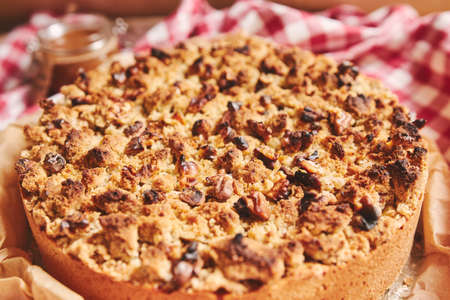 A closeup shot of a round apple pie topped with crumble and roasted nuts, on a towel