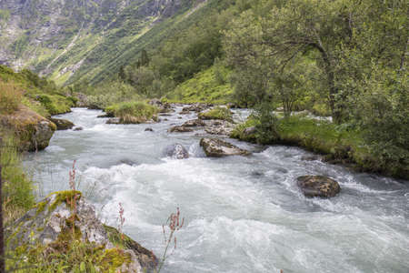 river that runs between high mountains of Norway during the summer 스톡 콘텐츠