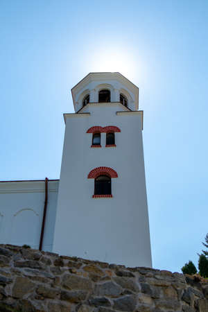A vertical low angle shot of a monastery in Bulgaria under the sunlight in a clear blue sky