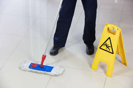A person cleaning the floor with a flat mop near a yellow caution wet floor sign