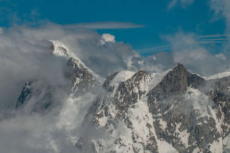 Dynamic close-up of mountains surrounded by clouds in the French Alps 免版税图像