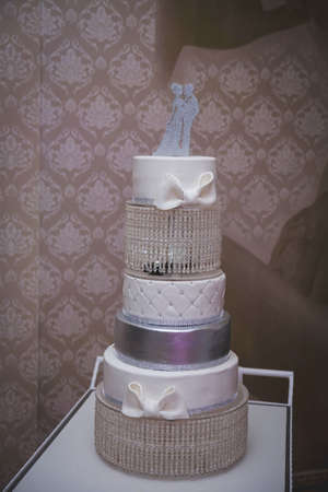 A vertical shot of a wedding cake with beautiful decorations and a topper
