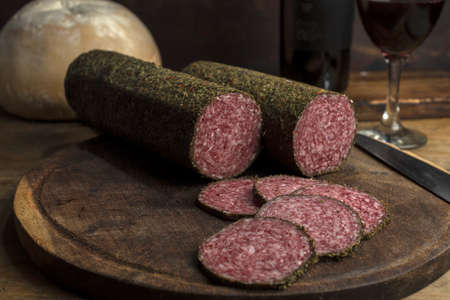 A closeup shot of rolls of smoked salami meat on a wooden board