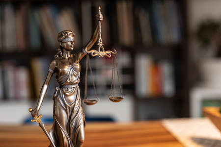 A selective focus shot of a statue of justice holding scales Stock Photo