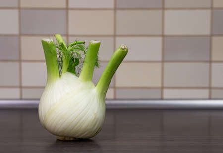 A closeup shot of a fresh whole fennel on a wooden surface