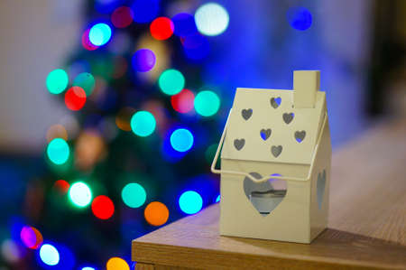 A close up shot of a Christmas decoration of a candle holder on the background of a Christmas tree