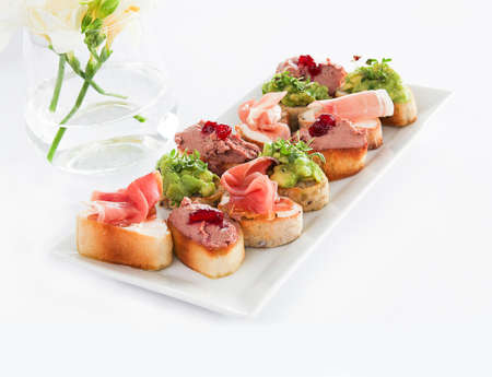A closeup of Bruschettas in a plate on the white table under the lights