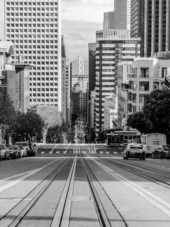A grayscale view of the railway of the San Francisco cable car system with city building and cars on Nob Hill
