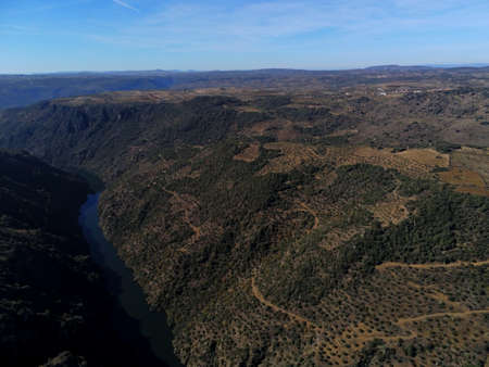 An aerial shot of forested mountains under a blue sky in Pereña de la Ribera. Salamanca, Spain