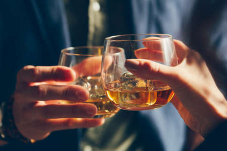 A closeup shot of two people clinking glasses with alcohol at a toast Reklamní fotografie