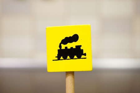 A closeup shot of a yellow wooden toy sign with a train icon