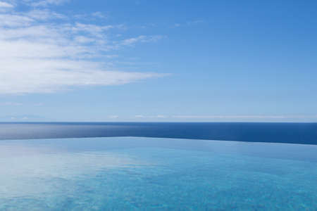 A blue sea with a clear sky with few clouds