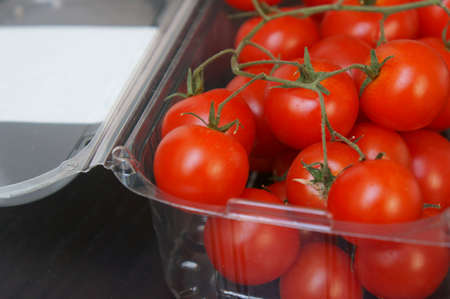 A closeup shot of cherry tomatoes in a plastic container