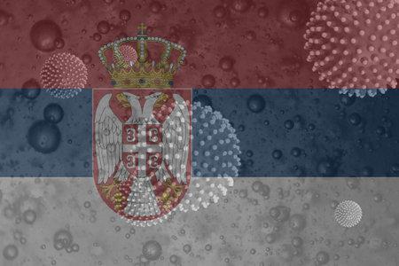 An illustration of the Coronavirus behind the Serbian flag 免版税图像