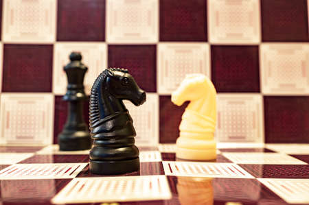 A selective focus closeup of black and yellow horses and a black bishop chess pieces on a chessboard