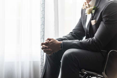 A handsome groom in a black suit praying before the wedding ceremony