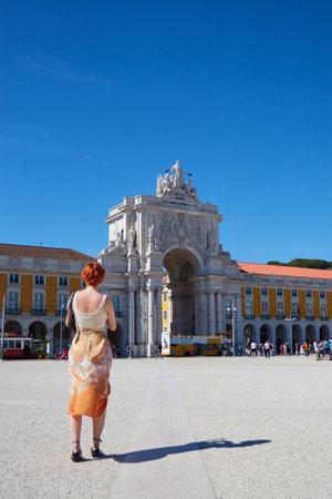 LISBON, PORTUGAL - Jun 11, 2019: Vertical shot of a beatiful woman stood infront of the Arco da Rua Augusta in Lisbon portugal
