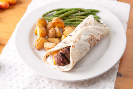 greek style hamburger rolled in a flatbread with fingerling pota