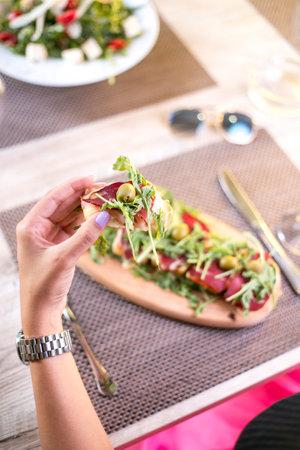A high angle shot of a woman eating an appetizer plate in a restaurant 免版税图像