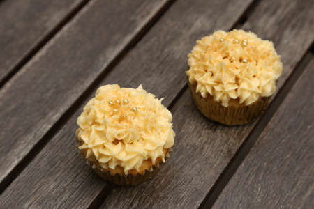 A closeup shot of two cupcakes with yellow cream on top