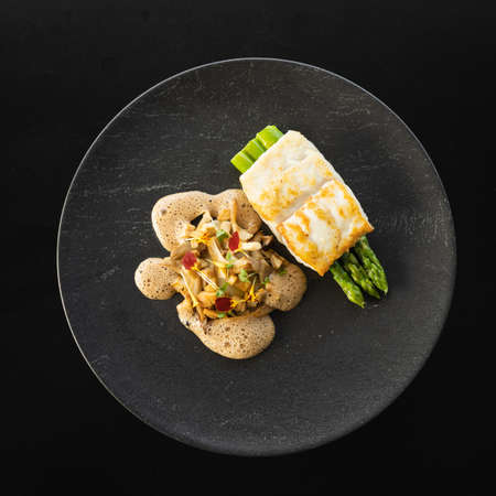 A top view of cooked tur meat with asparagus and tasty sauce