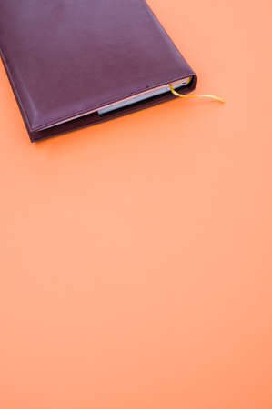 A top view closeup of a black notebook with a yellow bookmark isolated on an orange background