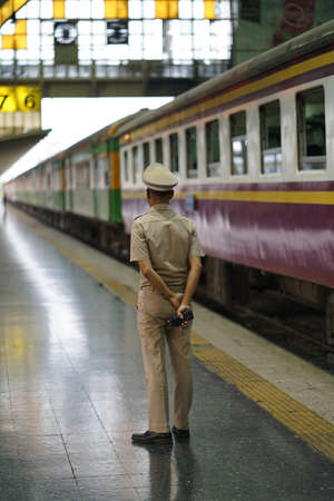 """officer waiting to give instructions for the train to leave Hua Lamphong"""" Bangkok railway station.amazing colours and architecture."""