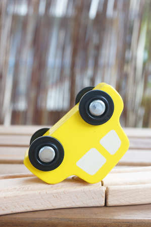 A closeup shot of a yellow toy car on a wooden surface