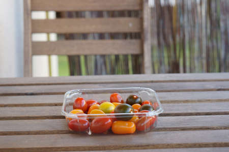 A closeup shot of oval tomatoes in plastic container on a wooden table