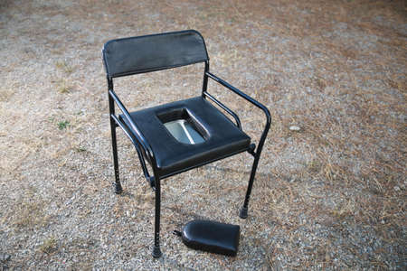 A mobile black leather potty chair outdoors