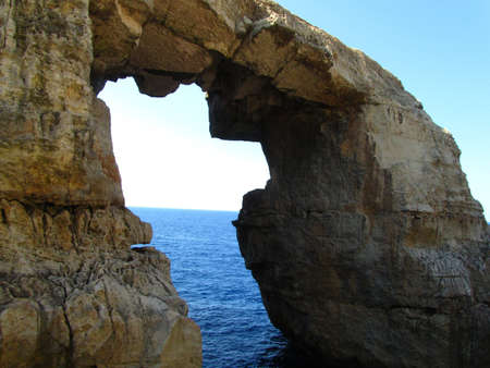 A natural rock arch with a sea erosion window on the Maltese Islands 免版税图像